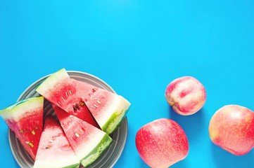 Flat lay food photo/ Plate with slices of juicy watermelon and red peaches on a blue background. Free space for text, mockup for design web site