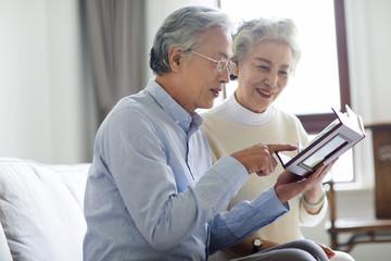 Happy senior couple looking at photo album