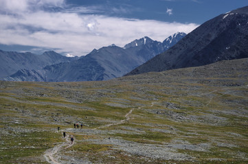 Group of people hikers with backpacks walking on trail in mountains at sunny day Altai Mountains Siberia, Russia