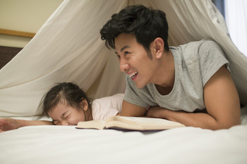 Smiling father and his daughter lying on bed while reading book