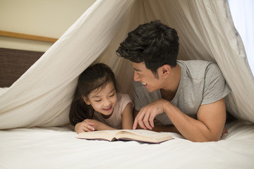 Little girl reading a book with father
