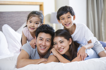 Cheerful young family on a bed
