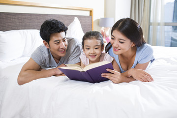 Cheerful young family reading a book on bed
