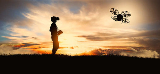 young operating of flying drone quadrocopter at sunset