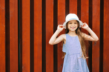 Children, facial expressions, emotions, fashion concept. Smiling happy girl with attractive appearance, wearing white hat and striped dress demonstrating her new fashionable clothes posing into camera