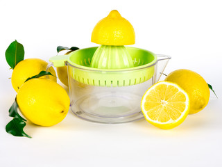 Hand juicer and lemons with green leaves over white background