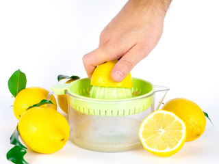 Males hand squeeze lemon on juiser
