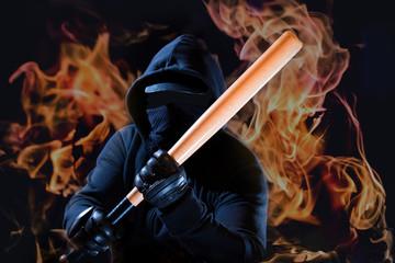 ein Hooligan greift mit einem Baseballschläger an