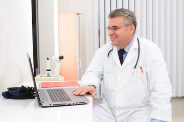 Doctor in his office with laptop