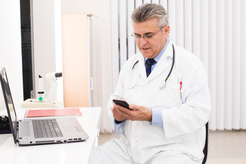 Doctor in his office with mobil phone