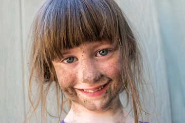 smiling girl with dirt on face closeup