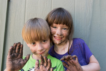 smiling boy and girl with muddy faces and hands