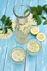 Two glasses of elderflower lemonade and carafe, top view