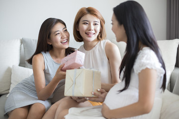 Young woman receiving baby shower gifts