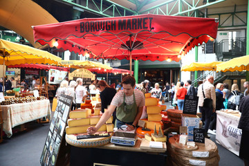A stall-holder sells cheese at Borough Market in London