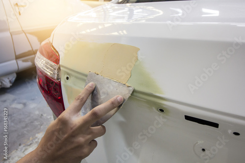 Repairing car body by puttying close up work after the