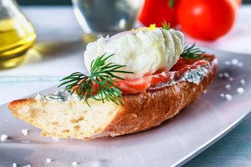 sandwich with ricotta cheese, salmon and poached egg on a plate