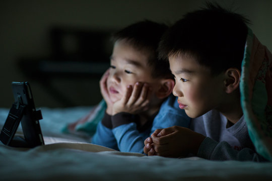 Boys watching digital tablet while lying on bed at home