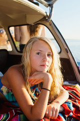 young girl lays in back of hatchback