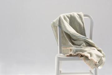Handmade wool and bamboo blanket on a metallic chair