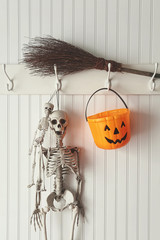 Toy skeletons and candy bucket hanging on coat hook