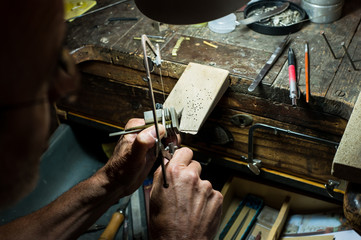 Jeweler making a necklace on his wokshop
