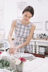 Young woman setting a table for dinning