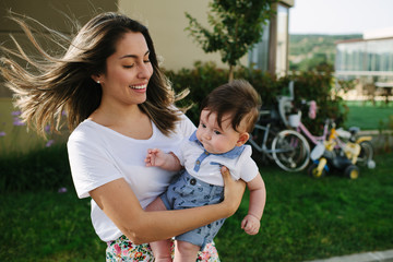 Beautiful woman carrying young child in front of an apartment building.
