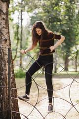 Teen girl climbs over the fence