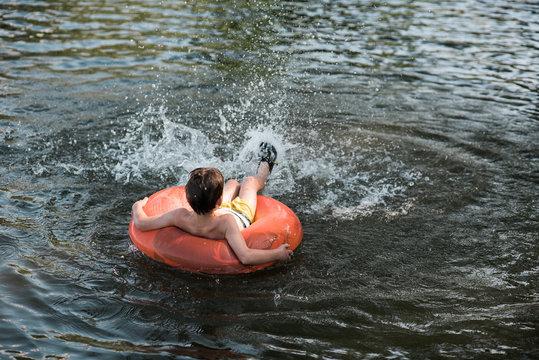 little boy floating on lake