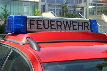german red fire department car with blue light