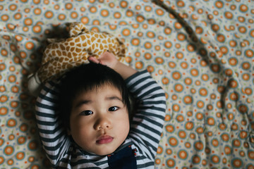 Asian American toddler boy laying on blanket with arms over head