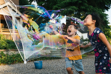 Asian American brother and sister popping a giant bubble outside