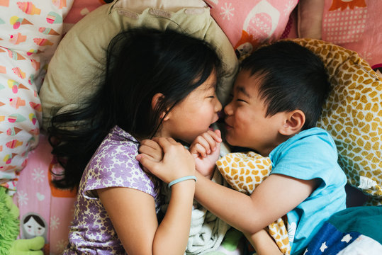 Asian American brother and sister happily cuddling together in bed