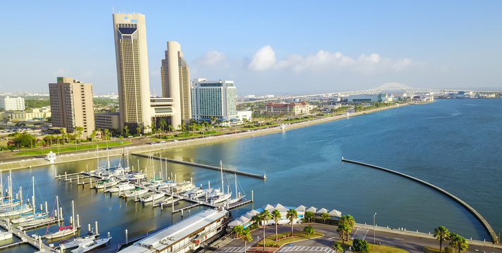 Panorama aerial view Bayfront area of Corpus Christi with skylines and marina piers row of boat, sailboat and yacht at sunrise. City harbor bridge far right in distance. A Texas city on Gulf of Mexico