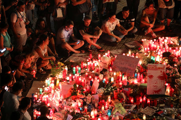 People gather around an impromptu memorial a day after a van crashed into pedestrians at Las Ramblas in Barcelona