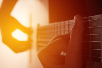 Man's hands playing on classical guitar against a background of sunlight (toned)