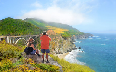 Couple relaxing on hiking trip. Man taking pictures with phone, woman looking at beautiful ocean mountains view.View from  highway 1 in California over Pacific Ocean. Big Sur, California, USA