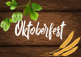 Banner for the Oktoberfest beer festival. Wheat, hops and beer on a wooden background of boards