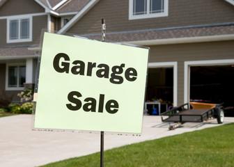 Garage sale sign in front of suburban garage
