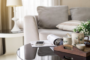 cup of tea on wooden tray on a round table with sofa in living room