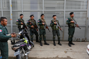 Cambodia police stand at a condo where they arrested dozens of young Chinese men and women working on a call centre to carry out a telephone and internet scam on victims in China in Phnom Penh