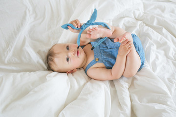 Pretty little baby in denim dress lays on a bed