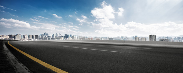Fototapete - empty road and cityscape of modern city against cloud sky