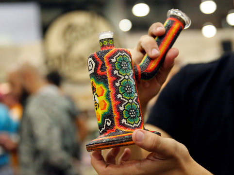 A participant shows a water pipe during the first day of the marijuana fair ExpoWeed in Mexico City