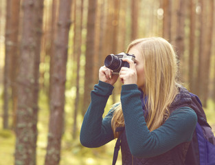 Happy, beautiful blond girl taking pictures in forest. Camp, tourism, hiking concept.
