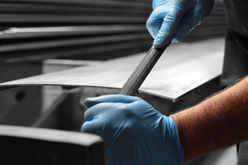 Man filing deburring a metal panel with a file