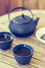Traditional japanese green tea prepared in cast iron teapot with organic dry green tea.