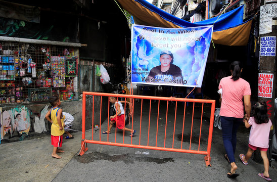 Residents walk past a streamer with the picture of Wilson Castillo, who was among the killed within a week of President Rodrigo Duterte's ruthless war on drugs, posted outside of their house in V. Mapa, metro Manila