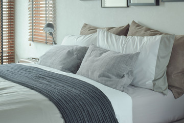 Dark gray bed runner with gray and brown pillows on bed